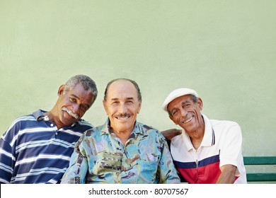 portrait of three senior men looking at camera against green wall and smiling. Horizontal shape, copy space