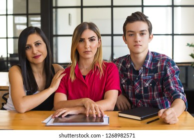 Portrait of three serious young Caucasian students sitting at table and looking at camera. Three friends at university or college. Education concept