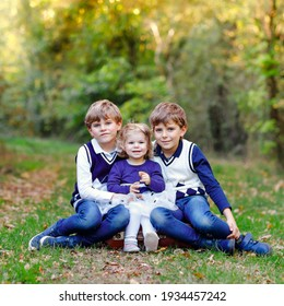 Portrait of three siblings children. Two kids brothers boys and little cute toddler sister girl having fun together in autumn forest. Happy healthy family playing, walking, active leisure on nature.