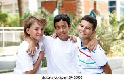 Portrait of three smiling handsome children of different races in outdoor .
