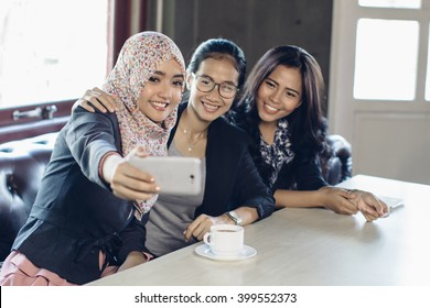 Portrait of three woman taking selfie at cafe together