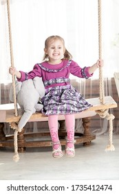 portrait of a three year old smiling little girl on a swing with a an elephant