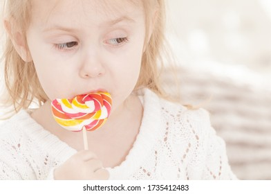portrait of a three year old smiling little girl eating a candy