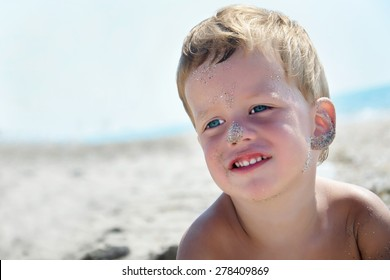 Portrait of three years cute boy on beach, face in sand