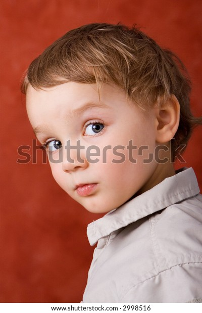 Portrait of a three years old blond caucasian boy against a red background.