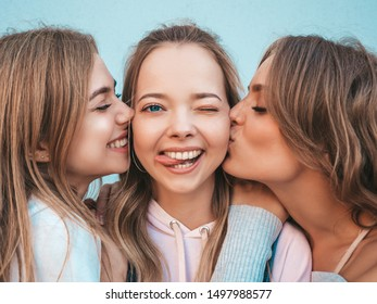 Portrait of three young beautiful smiling hipster girls in trendy summer clothes. Sexy carefree women posing in the street.Positive models kissing their friend in cheek