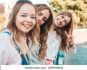 Portrait of three young beautiful smiling hipster girls in trendy summer clothes. Sexy carefree women posing on the street background.Positive models having fun.Hugging