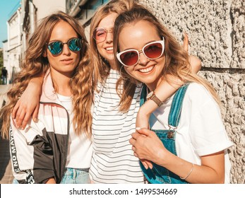 Portrait of three young beautiful smiling hipster girls in trendy summer clothes. Sexy carefree women posing in the street near wall.Positive models having fun in sunglasses.Hugging