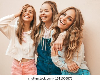 Portrait of three young beautiful smiling hipster girls in trendy summer clothes. Sexy carefree women posing on the street near wall.Positive models having fun.Hugging