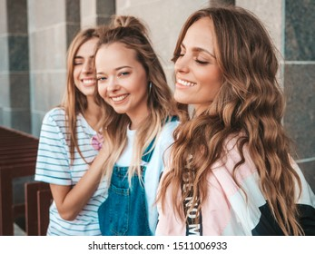 Portrait of three young beautiful smiling hipster girls in trendy summer clothes. Sexy carefree women posing on the street background.Positive models having fun