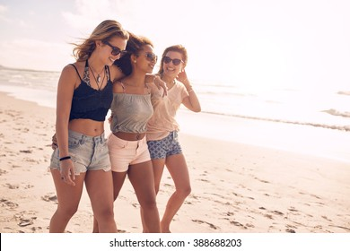 Portrait of three young female friends walking on the sea shore. Multiracial young women strolling along a beach on a summer day.