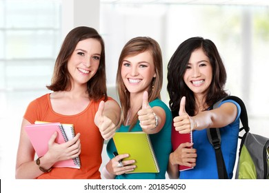 Portrait of a three young female student together showing thumbs up