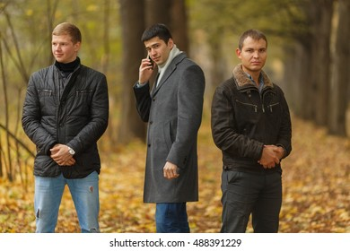 Portrait of three young men in autumn park, one talking on phone, one looking at camera, one looking to side