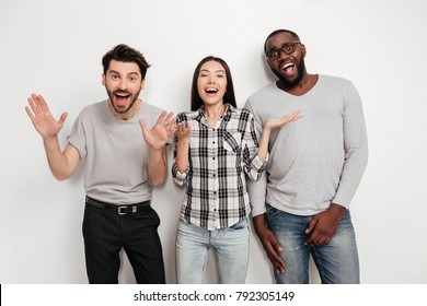 Portrait of three young multinational friends standing together and happily looking in camera with open mouth on white background in studio