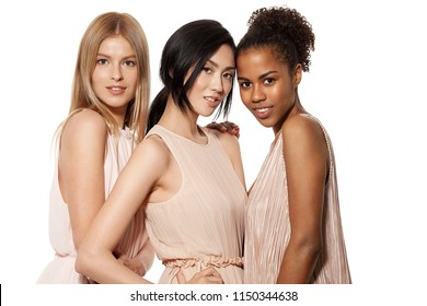 Portrait of three young multinational women posing at studio. Cheerful multiracial female friends looking at camera with gladness. Isolated on white background
