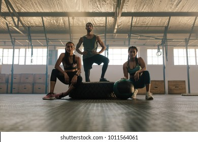 Portrait of three young people resting and looking at camera after training session in gym. Small group of people after training at health club.