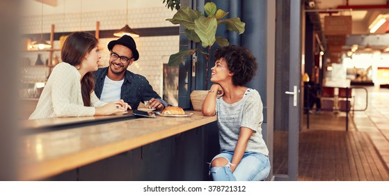 Portrait of three young people sitting together at a cafe. Group of young friends meeting in a coffee shop.