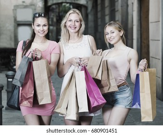 portrait of three young smiling girls standing with shopping bags outdoors together