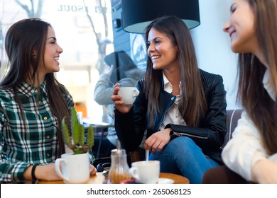 Portrait of three young woman drinking cofee and speaking at cafe shop.