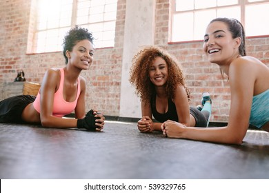 Portrait of three young women in fitness class looking at camera and smiling. Female friends exercising together in fitness class.