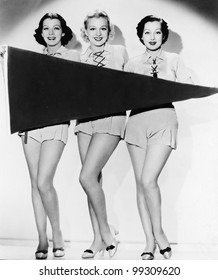Portrait of three young women holding a banner and smiling