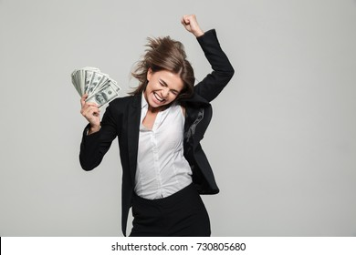 Portrait of a thrilled excited businesswoman in suit holding bunch of money banknotes and celebrating isolated over white background