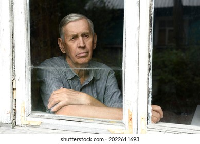 Portrait through the glass window. A sad elderly man of 80 years old, sitting in an old house.