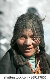 Portrait of Tibetan Woman wearing Elaborate-Braids Hairstyle, Saga Dawa Festival, Mt.Kailash, Tarboche Valley, Tibetan Autonomous Region, China. May 30, 2007.
