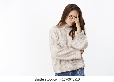 Portrait of tired and annoyed woman hiding eyes as being embarrassed making facepalm gesture tilting head down standing upset and irritated over gray background in sweater and glasses