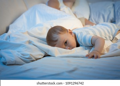 Portrait of tired baby lying on big bed at night and looking in camera