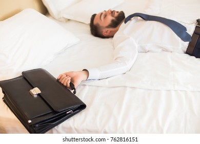 Portrait of tired bearded businessman laying on hotel bed relaxing after business trip focus on leather case in foreground