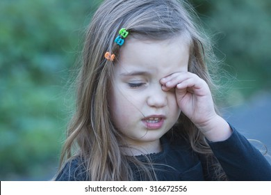 portrait of tired or bored little girl wiping her eye