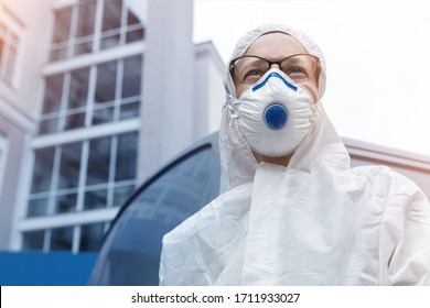 Portrait of tired exhausted pensive female doctor, scientist or nurse wearing face mask and biological hazmat ppe suit looking forwad with anxious aware outdoor. Coronavirus covid-19 outbreak danger