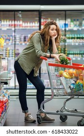 Portrait of a tired exhausted woman leaning on a shopping cart at the supermarket and looking at camera