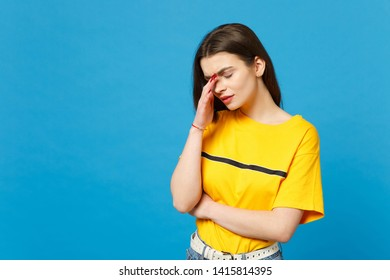 Portrait of tired exhausted young woman in vivid casual clothes keeping eyes closed, putting hand on nose isolated on bright blue background in studio. People lifestyle concept. Mock up copy space