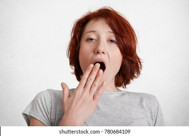 Portrait of tired female looks sleepy, yawns, covers mouth with hand, worked all night, isolated over white concrete background. Horizontal shot of fatigue redhead young woman feels exhaustion