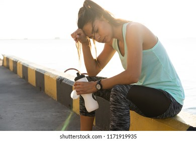 Portrait of tired fitness young woman outdoors in the city. Young woman runner resting after workout session on sunny morning near the sea port