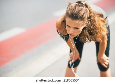 Portrait of tired fitness young woman outdoors in the city catching breathe