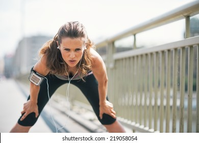 Portrait of tired fitness young woman catching breathe
