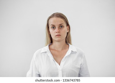 Portrait of a tired girl without makeup on a white background