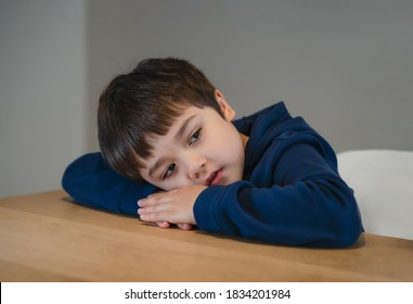 Portrait tired kid lying head down on his arm lookig out deep in throught, Bored child laying head on table with unhappy face, Lonely Young boy with sad face sitting alone, Health metal concept