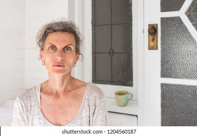 Portrait of tired looking middle aged woman with grey hair in sunroom at home (selective focus)