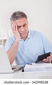 Portrait Of Tired Mature Man Doing Finances