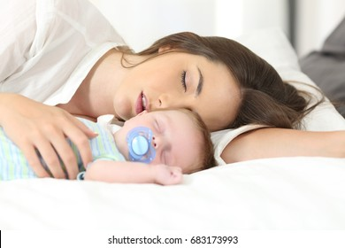 Portrait of a tired mother sleeping with her baby on a bed at home