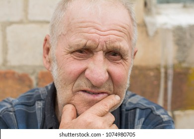 portrait of a tired old man or an elderly grandfather in the background of his village house