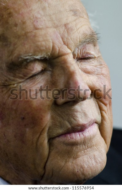 Portrait of a tired old man in his 90's, isolated on white background.
