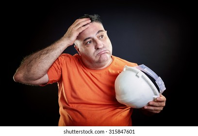 Portrait of a tired overweight construction worker, removing his helmet and wiping his brow with his hand, all over black background.