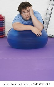 Portrait of a tired overweight man resting on exercise ball in health club