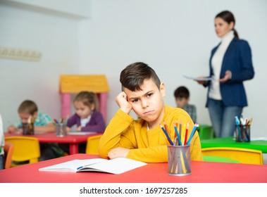 Portrait of tired schoolboy sitting in classroom elementary school