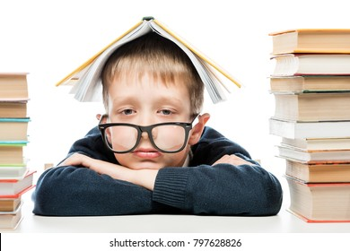 portrait of a tired schoolboy wearing glasses with a book on his head